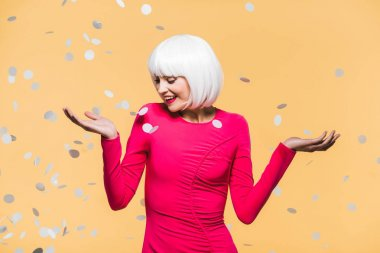 cheerful pretty girl in red dress and white wig posing with holiday confetti, isolated on yellow