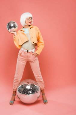 happy girl in white wig posing with disco balls on pink