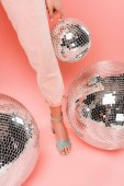 partial view of stylish girl posing with disco balls on pink