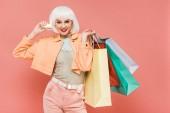 vonzó lány fehér parókát a bevásárló táskák és hitelkártya, izolált rózsaszín