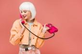 usmívající se dívka v bílé paruce, mluvící na retro telefonu, izolovaná na růžovém