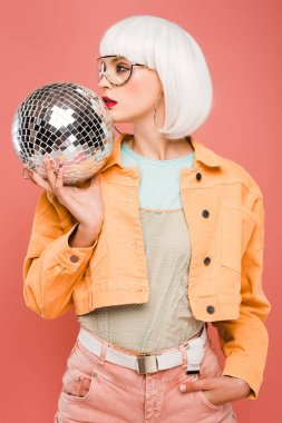 stylish girl in white wig posing with disco ball, isolated on pink