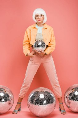 beautiful fashionable girl in white wig posing with disco balls on pink