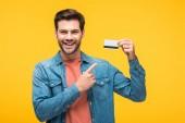 schöner Mann zeigt mit dem Finger auf Kreditkarte isoliert auf gelb