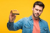 Verwirrter gutaussehender Mann mit gelber Kreditkarte