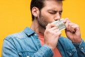 handsome man kissing dollar banknotes isolated on yellow