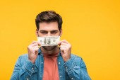pohledný muž pokrývající tvář s penězi izolovanými na žlutém