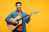 handsome smiling man playing acoustic guitar Isolated On yellow
