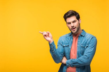 Confused handsome man pointing with finger and looking at camera isolated on yellow stock vector