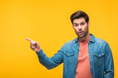 surprised handsome man pointing with finger isolated on yellow