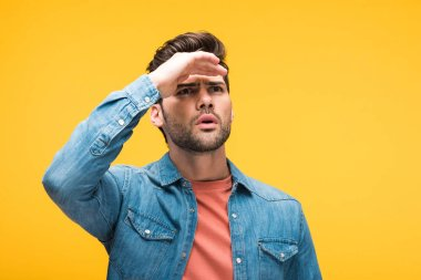 Confused handsome man with hand on forehead isolated on yellow stock vector