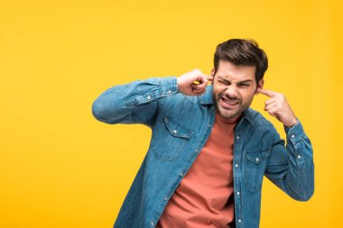 dissatisfied handsome man plugging ears with fingers isolated on yellow