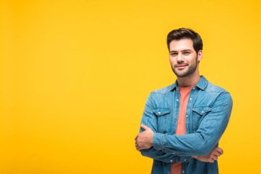 happy handsome man with crossed arms looking at camera isolated on yellow