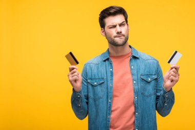 Confused handsome man holding credit cards isolated on yellow stock vector