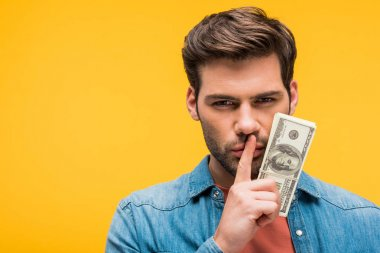 Handsome man doing silence gesture and holding dollar banknotes isolated on yellow stock vector