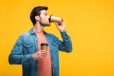 handsome man drinking coffee to go isolated on yellow with copy space