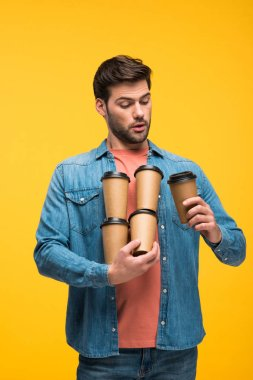 handsome man holding paper cups with coffee to go isolated on yellow