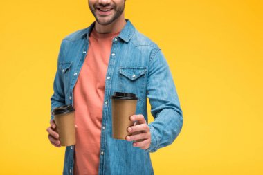 Cropped view of smiling man holding coffee to go isolated on yellow stock vector
