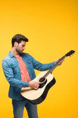 handsome man playing acoustic guitar On yellow