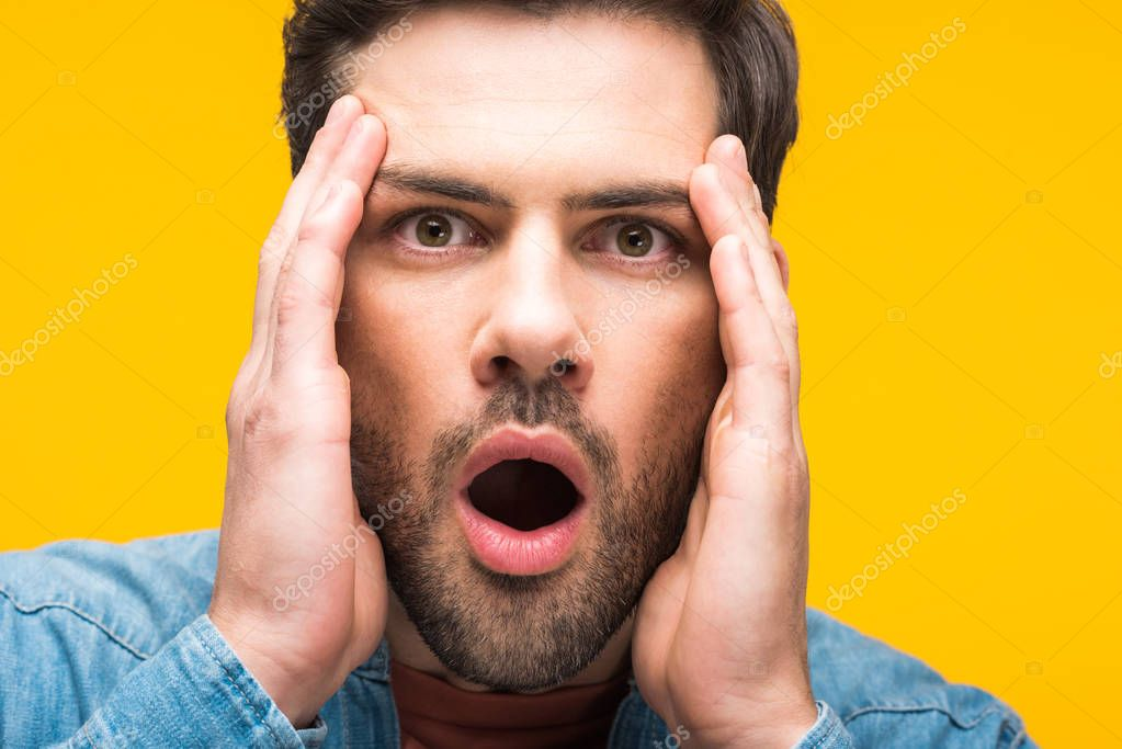 Shocked handsome man with hands on head isolated on yellow stock vector