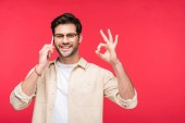šťastný muž, který mluví na telefonu a dělá ok nápis izolovaný na růžovém