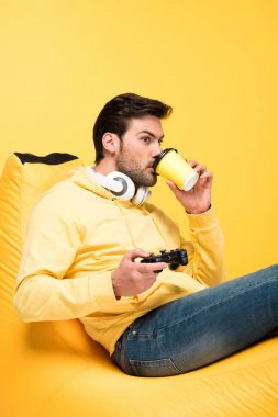KYIV, UKRAINE - APRIL 12: man drinking coffee to go on bean bag chair and playing Video Game isolated on yellow stock vector
