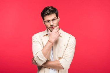 Pensive man in glasses touching chin isolated on pink stock vector
