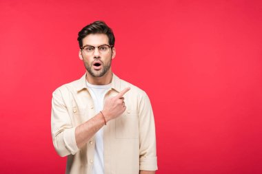 surprised handsome man pointing with finger On pink with copy space
