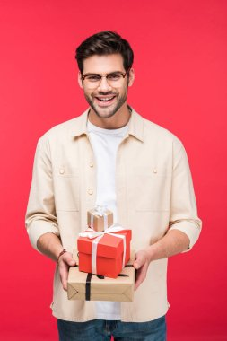 Handsome smiling man holding presents Isolated On pink stock vector