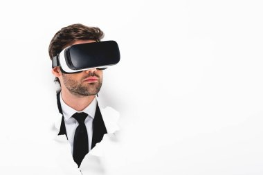 Man in formal wear and Virtual reality headset behind hole in paper wall on white with copy space stock vector