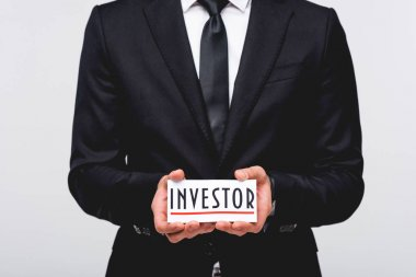 cropped view of businessman in suit hodding card with investor word isolated on grey