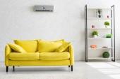 Fotografie geräumiges Wohnzimmer mit Klimaanlage an weißer Wand, gelbem Sofa und Ablage