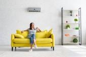 Fotografie schöne junge Frau sitzt auf gelbem Sofa unter Klimaanlage in geräumiger Wohnung