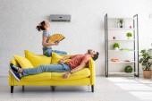 kimerült ember feküdt a sárga kanapé légkondicionáló alatt mellett nő kézi ventilátor