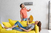 Photo woman and lying on yellow sofa and man with newspaper suffering from heat at home