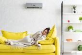 gefrorene Frau wärmen mit Decke, während auf gelbem Sofa unter Klimaanlage zu Hause liegen
