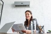 usmívající se obchodové ženy při sezení na pracovišti pod klimatizací