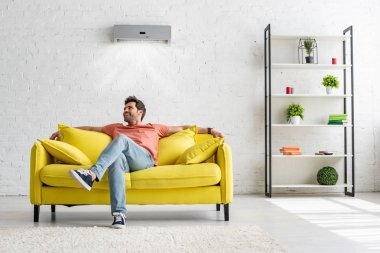 Smiling handsome man sitting on yellow sofa under air conditioner at home stock vector