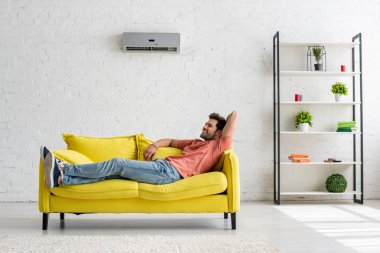 handsome smiling man lying on yellow sofa under air conditioner at home