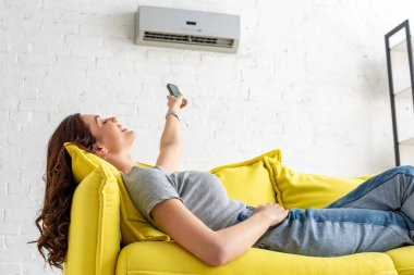 attractive young woman relaxing under air conditioner and holding remote control