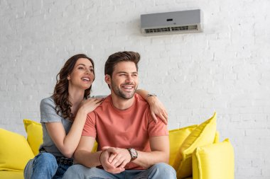 happy couple sitting on yellow sofa under air conditioner at home