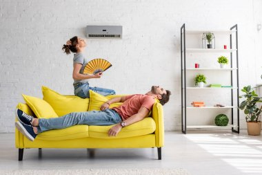exhausted man lying on yellow sofa under air conditioner near woman with hand fan