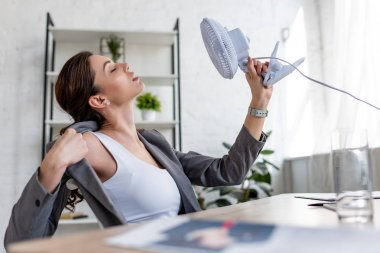selective focus of beautiful businesswoman suffering from heat and holding electric fan
