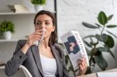 gyönyörű üzleti nő iszik vizet üvegből és integetett üzleti újság, miközben szenved hőt az irodai