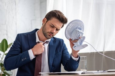 handsome businessman suffering from heat in office and holding electric fan