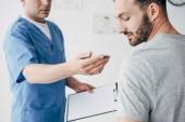 Physiotherapeut mit Diagnose und Pen gestikulieren in der Nähe von Patient im Krankenhaus