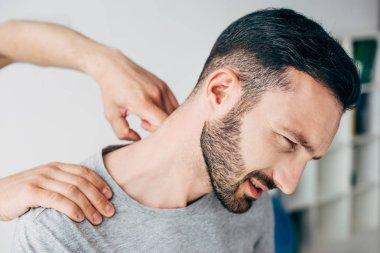 chiropractor massaging neck of bearded man in hospital