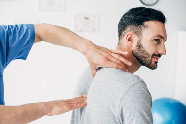 chiropractor massaging neck of good-looking man in hospital