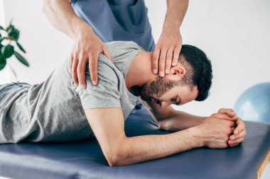 chiropractor massaging shoulder and neck of man on Massage Table in hospital
