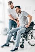 Fotografie Physiotherapeut hilft behinderten Menschen im Rollstuhl bei der Genesung